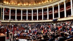 Members of Parliament react after the speech of French Prime Minister Edouard Philippe (L) during a debate at the National assembly in Paris on July 31, 2018