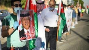Un manifestant tient le portrait du roi Abdallah de Jordanie et le drapeau national lors de la manifestation à Amman, le 27 juin 2020.