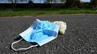 Cette photo prise le 10 avril 2020 montre des gants en latex et un masque jetés sur un trottoir à Lille, dans le nord de la France, en pleine pandémie du nouveau coronavirus.