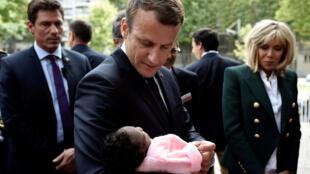 图为法国总统马克龙与夫人参观巴黎一家医院怀抱一新生儿照片