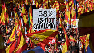 "Protesters wave Spanish and Catalan Senyera flag while holding a sign reading ""38 percent is not Catalonia"" in reference to a referendum voter turnout during a pro-unity demonstration in Barcelona on October 29, 2017."