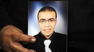 Abdullah Reda al-Hamamy's photo held by his father Reda