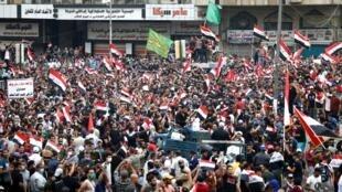 Manifestantes portan banderas iraquíes durante una protesta contra la corrupción, la falta de trabajo y los servicios deficientes, en Bagdad, Iraq, el 25 de octubre de 2019.