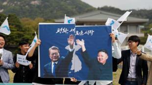 និស្សិត លើកបដា រូបលោក Moon Jae-in និង Kim Jong Un តំណាងសន្តិភាពផ្សះផ្សាគ្នា។  ថ្ងៃទី២៦មេសា ២០១៨