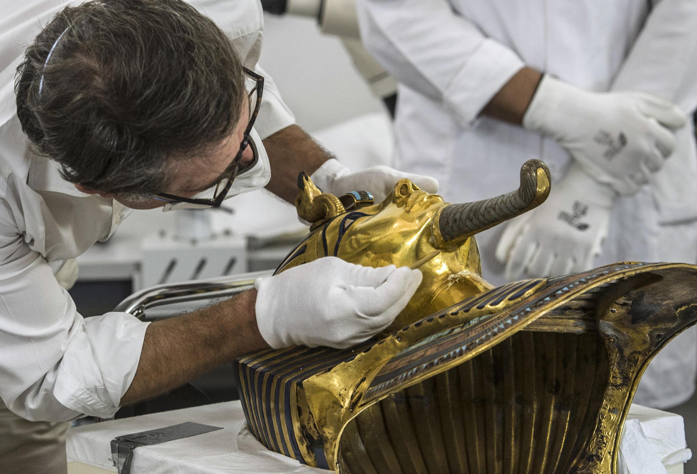 Au musée égyptien du Caire, Christian Eckmann, à l'aide d'un simple bâtonnet de bois, procède à la restauration du masque d'or de Toutankhamon abîmé, le 20 octobre 2015.