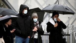Tourists wearing masks walk away from the Louvre as the staff closed the museum during a staff meeting about the coronavirus outbreak, in Paris, France, March 2, 2020.
