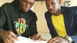 Meddie Kagerea kushoto akisaini mkataba wa kuitumikia Simba