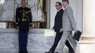 O presidente François Hollande acompanhado do General Benoit Puga na saída do conselho de minstros no Palácio do Eliseu, neste 17 de dezembro de 2014.
