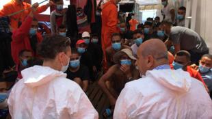 Après une semaine d'attente en mer, les personnes secourus sur le pont de l'«Ocean Viking» rencontrent un médecin italien, le 4 juillet 2020
