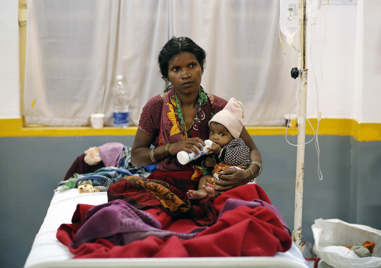 Une femme qui s'est faite stériliser donne le biberon à son enfant, à Bilaspur, dans l'est de l'Inde, le 14 novembre 2014.