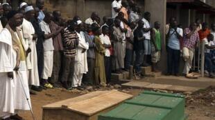 Des Banguissois sont rassemblés autour de cercueils de deux hommes tués dans le quartier du PK5, le 23 mars 2014.