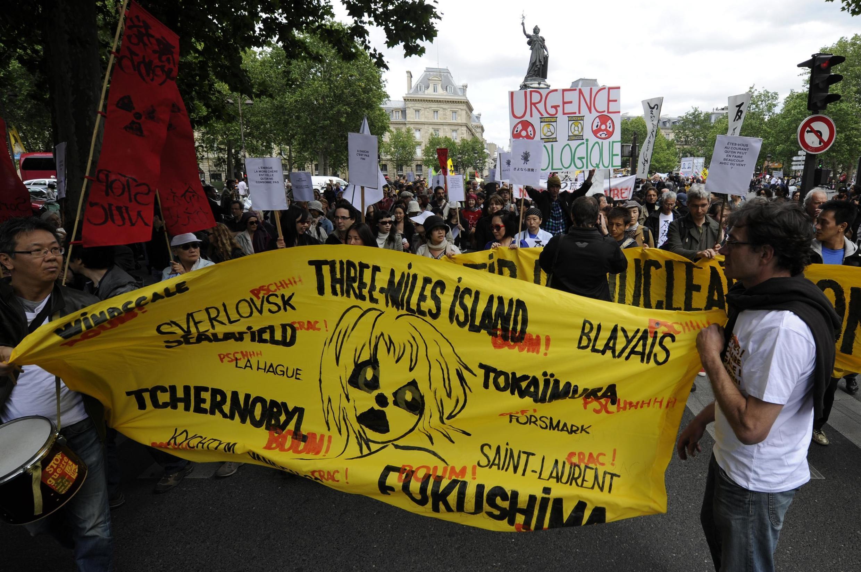 Faixas de manifestantes em Paris com tragédias nucleares mundiais.