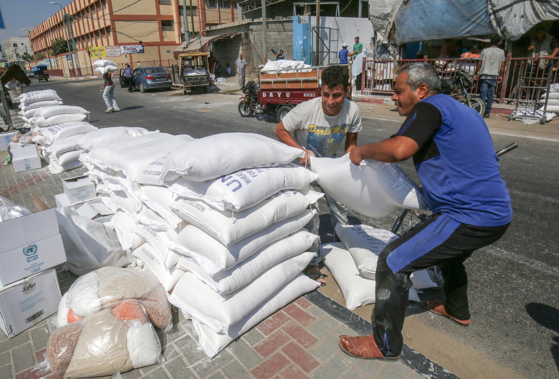 Des Palestiniens empile des sacs de farine devant un centre de distribution de l'UNRWA dans le camp de réfugiés de Bureij au centre de la Bande de Gaza, le 31 juillet 2019.
