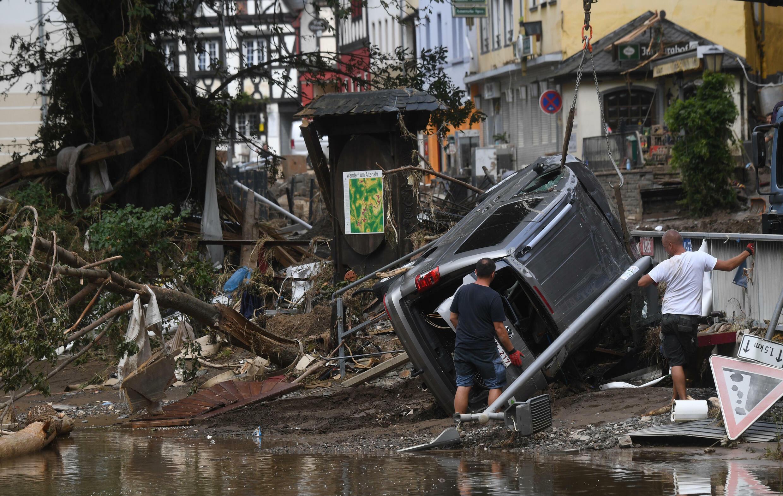 Dos hombres observan un automóvil arrastrado por las inundaciones el 19 de julio de 2021 en la ciudad de Altenahr, al oeste de Alemania