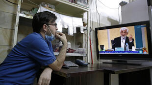 An Iranian man watches the first presidential candidates' debate at a shop in Tehran on June 5, 2021. Iranians are set to elect a successor to President Hassan Rouhani on June 18