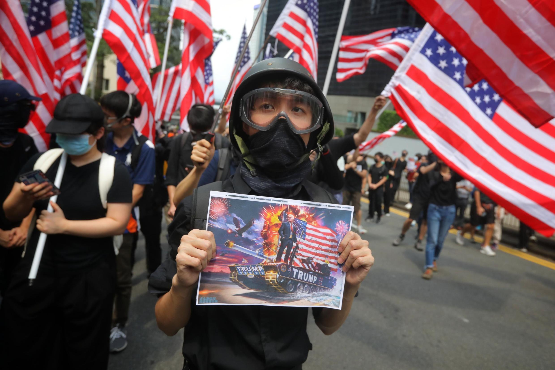 Les manifestants pro-démocratie agitent des drapeaux américains en marchant vers le consulat des États-Unis à Hong Kong pour appeler Washington à faire pression sur Pékin pour répondre à leurs revendications, le 8 septembre 2019.