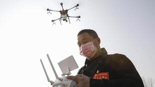 Un résident local utilisant un drone pulvérise du désinfectant dans un village de Pingdingshan, dans la province centrale du Henan, en Chine, le 31 janvier 2020, lors de l'épidémie de virus dans la ville de Wuhan, à Hubei.