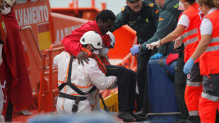 A man is helped by rescuers after arriving on a rescue boat at the port of Malaga in Spain