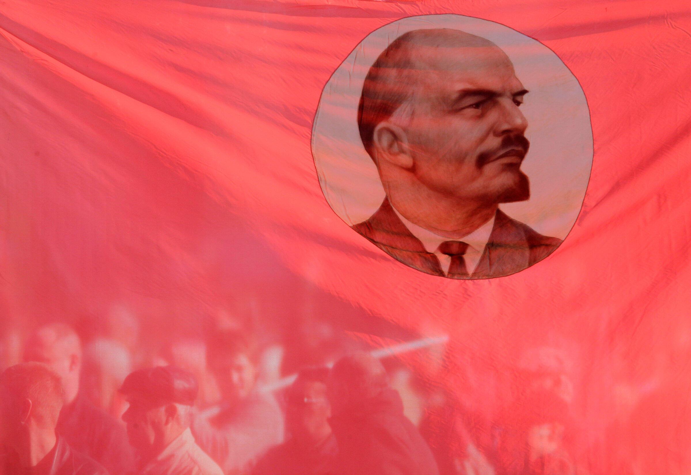 Partidários do comunismo são vistos através da bandeira vermelha, com o retrato de Lênin, em Stavropol, em 7 de novembro de 2010.
