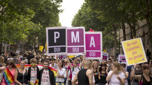 Assisted medical procreation, or PMA, has been a demand from LGBT activists in France. Marchers in the Paris Gay pride parade in 2013 hold signs calling for it to be extended to all