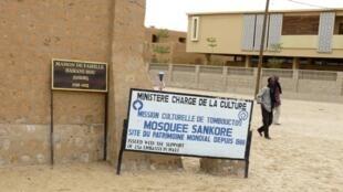 Dans les rues désertes de Tombouctou, devant des panneaux indiquant des sites du patrimoine mondial.