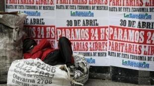 Quartier des banques de Buenos Aires, le 25 avril 2019: les affiches annoncent une grève pour le 30 avril alors que se repose un cartonero sur son sac de déchets.
