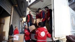 Une centaine de camions chargés d'aide se dirigent 17 février vers des villes assiégées de Syrie dans un climat de vive tension entre Damas et l'émissaire de l'ONU Staffan de Mistura. Ici un camion du Croissant Rouge syrien à Douma, une banlieue de Damas.