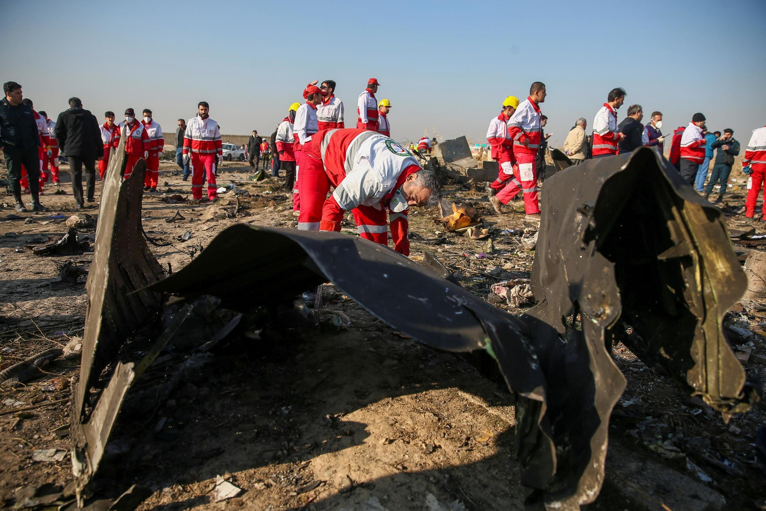 Red Crescent workers check the debris of the Ukraine International Airlines plane, which crashed after take-off from Iran's Imam Khomeini airport.