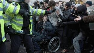 Demonstrators clash with police during a protest in London over a university fee hike bill