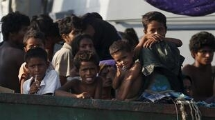 Migrants are seen aboard a boat tethered to a Thai navy vessel, in waters near Koh Lipe island, May 16, 2015. A boat crammed wit