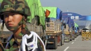 Một người lính Hàn Quốc quan sát các đoàn xe tải chở bột mì sang Bắc Triều Tiên đang qua cầu Tongil tại Paju, miền bắc Hàn Quốc ngày 16/9/2010.