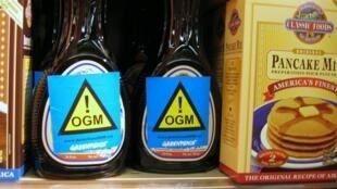 Etiquetas de Greenpeace alertan en botellas de jarabe en un supermercado sobre contenido de OGM.