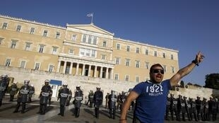 Riot police cordon off the Greek parliament from demonstrators opposed to the bail-out terms