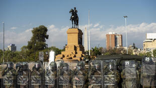 Members of Chile's Carabineros riot police stand guard  in Santiago's Plaza Italia during anti-government protests in October 2020