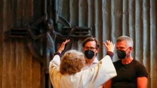 Une femme qui aide à la pastorale bénie un couple homosexuel dans une église de Cologne, en Allemagne, le 10 mai 2021.