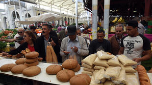 Tunisians buy bread at a market in Tunis during the first day of Ramadan.