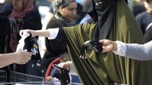 Una mujer lleva el velo integral en el mercado de Vénissieux (periferia de la ciudad de Lyon).