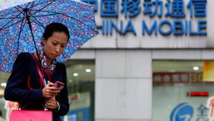 Une passante utilise son portable devant une boutique China Mobile au centre de Shanghaï.