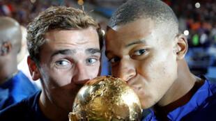 Kylian Mbappe y Antoine Griezmann besan el trofeo de la Copa del Mundo mientras celebran durante una ceremonia después del partido contra Holanda, donde los galos ganaron 2 - 1.