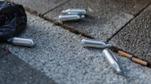 Des cartouches de siphon à chantilly, utilisées pour inhaler le protoxyde d'azote, abandonnées dans la rue.