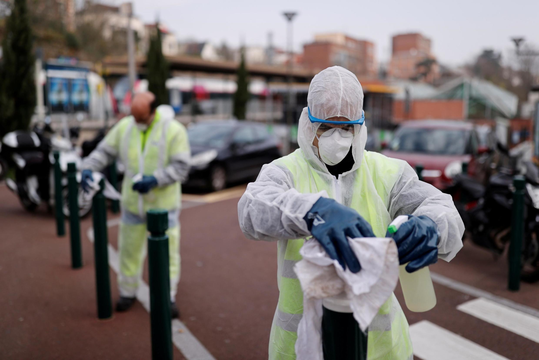 Funcionários municipaus desinfetam estruturas urbanas em Suresnes, periferia de Paris.