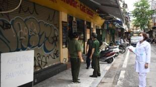 Nhân viên y tế kiểm tra các cửa hàng ăn buộc phải đóng cửa do tình hình dịch Covid-19 diễn biến phức tạp, tại Hà Nội, Việt Nam, ngày 25/05/2021.