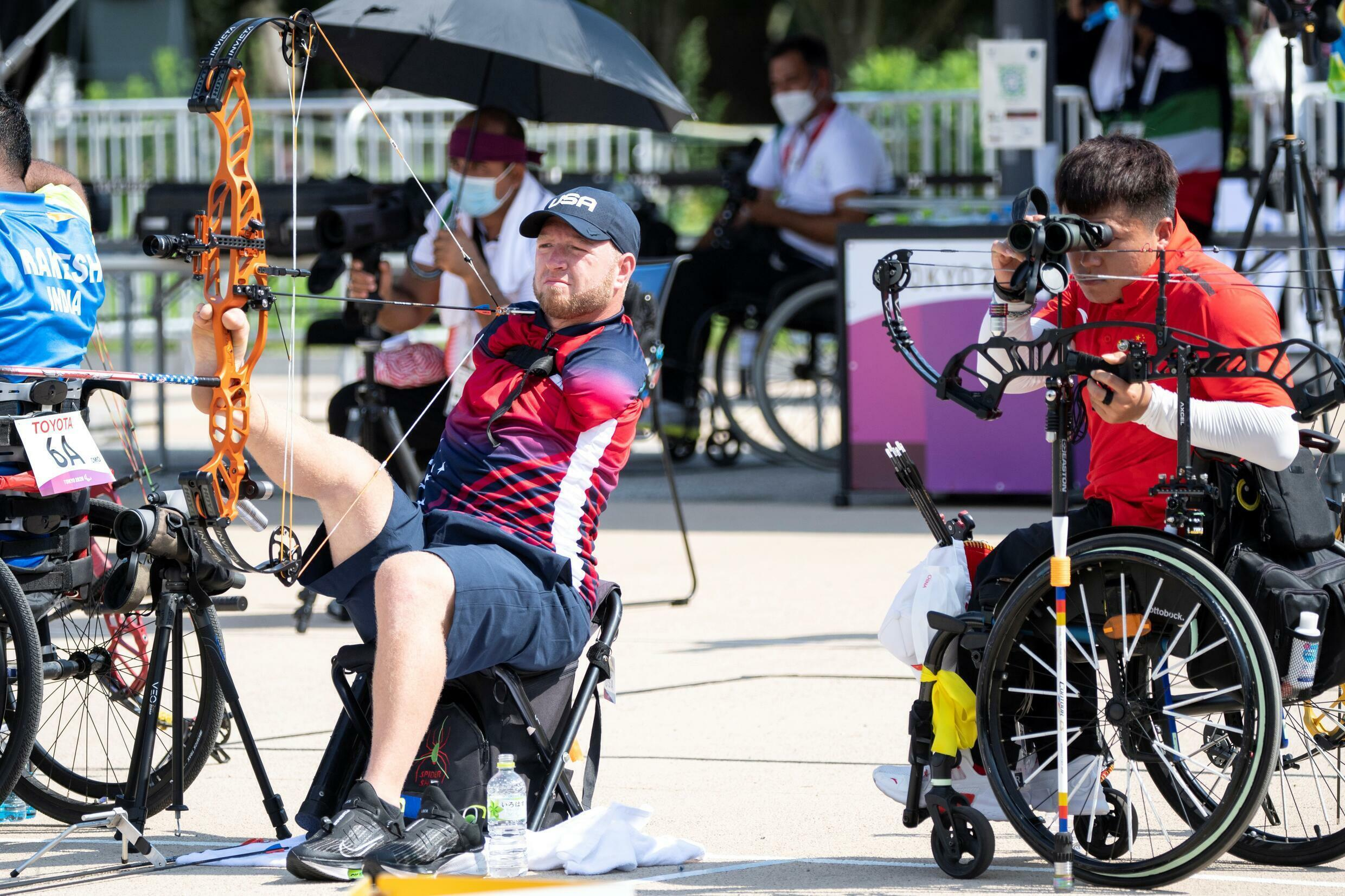 USA's Matt Stutzman (L) and China's Ai Xinliang (R) compete in the men's archery individual ranking round during the Tokyo 2020 Paralympic Games at the Yumenoshima Park archery field in Tokyo on August 27, 2021.
