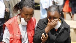 Родственницу одного из погибших при атаке на университет в Гариссе сопровождает сотрудник Красного Креста, 4 апреля 2015 г.