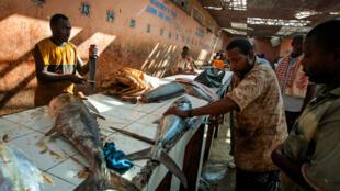 Traders cut and fillet fish inside Mogadishu's fish market