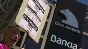 Homem protesta contra sede do banco Bankia na Espanha. O banco é o quarto maior do país.