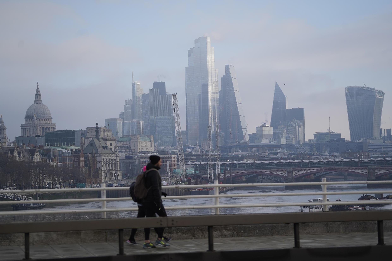 Dos personas cruzan un puente sobre el río Támesis con los rascacielos de la City al fondo, el 31 de diciembre de 2020 en Londres
