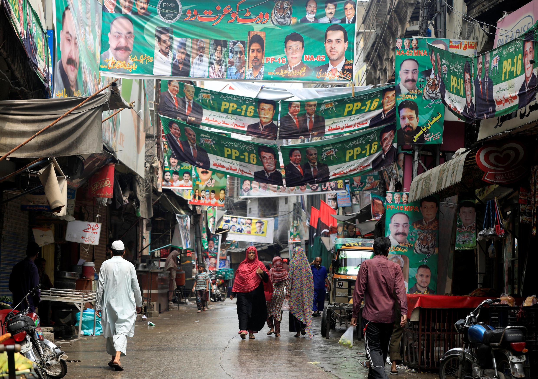 Des passants dans une rue tapissée d'affiches électorales dans le cadre des législatives, à Rawalpindi, au Pakistan.