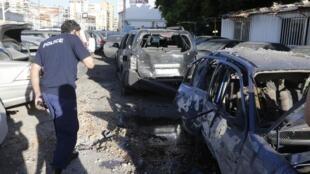 Un policier inspecte une carcasse de voiture après l'explosion de deux roquettes dans le sud de Beyrouth, dimanche 26 mai 2013.
