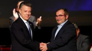 Le président colombien Juan Manuel Santos (g), et le chef des FARC Rodrigo Londono, alias Timochenko, le 24 novembre 2016 à Bogota.